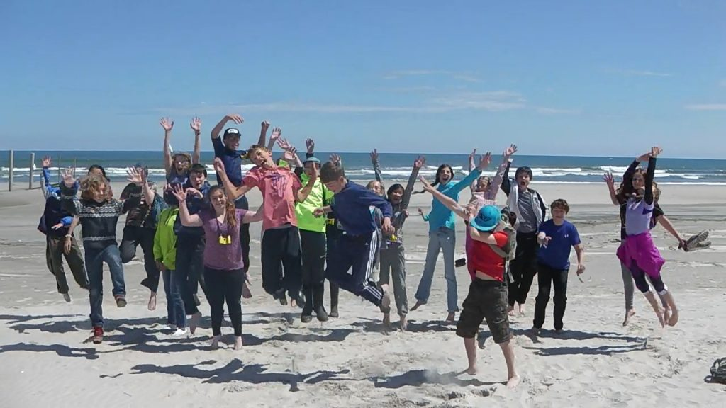 RVCS Students jumping in air during a service learning to the the Delaware Bay