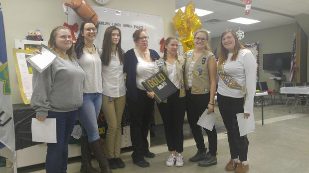 Girl Scout leader Monica Bonnie Anderson stands with Lara Watrous as she displays her Gold Award. They are flanked by other troop members